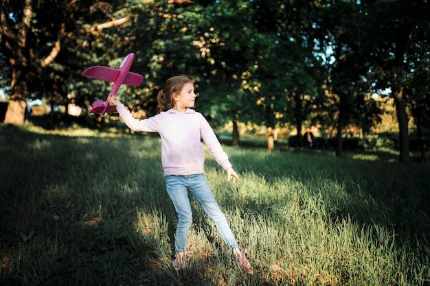 Menina lança um avião de brinquedo no ar no parque Foto Premium