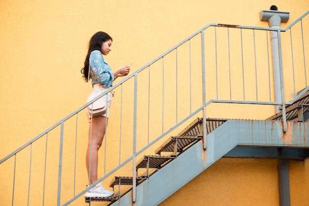 Menina lateral de pé na escada Foto gratuita