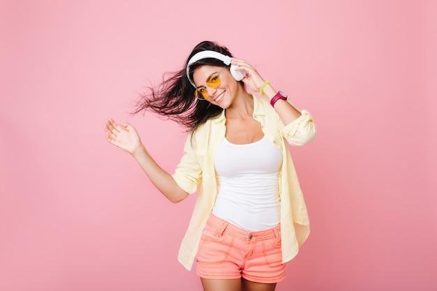 Menina latina elegante de bom humor, posando para a foto e dançando. entusiasta jovem hispânica com roupa de verão, relaxando enquanto ouve a música favorita. Foto gratuita