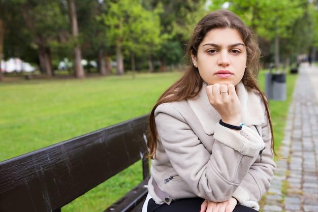 Menina latina pensativa esperando alguém no parque Foto gratuita