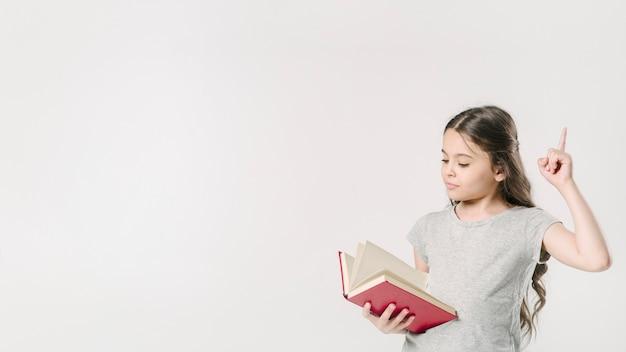Menina, leitura, e, levantamento, dedo, em, estúdio Foto gratuita