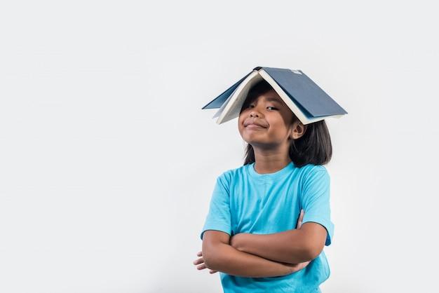 Menina lendo livro em estúdio tiro Foto gratuita