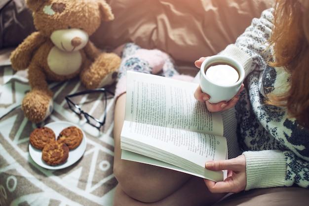 Menina lendo livro na cama com meias quentes, bebendo café Foto Premium