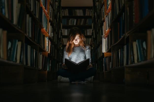 Menina lendo um livro na biblioteca sentada no chão. a menina na biblioteca Foto Premium