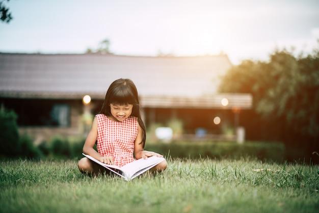 Menina lendo um livro no jardim da casa Foto gratuita