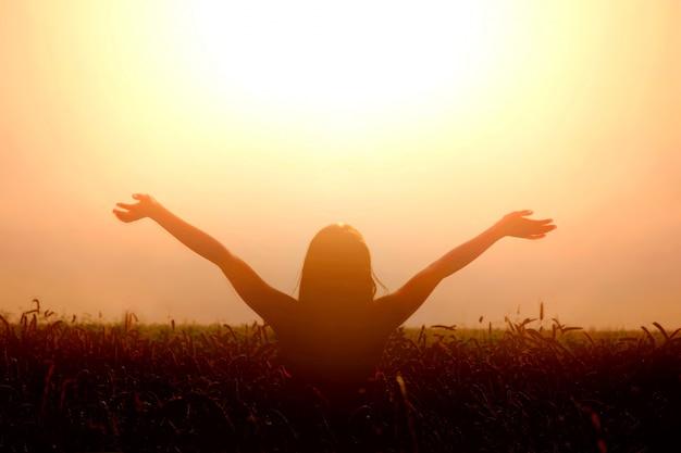 Menina levanta as mãos para o céu e sente liberdade. Foto gratuita