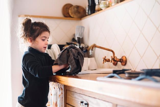 Menina, limpando, dela, mão, com, toalha, em, cozinha Foto gratuita