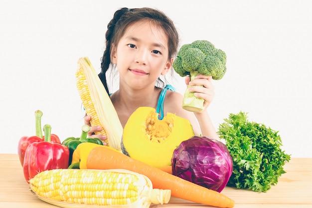 Menina linda asiática mostrando desfrutar de expressão com legumes coloridos frescos Foto gratuita