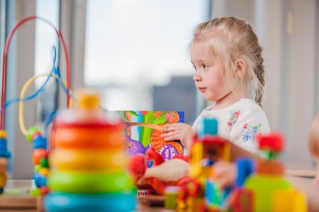 Menina linda com brinquedos no jardim de infância Foto Premium