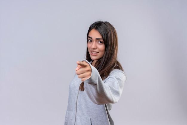 Menina linda com capuz cinza olhando para a câmera com uma expressão de insatisfação e apontando para a câmera em pé sobre um fundo branco Foto gratuita