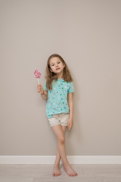 Menina linda com pirulitos em fundo bege Foto gratuita