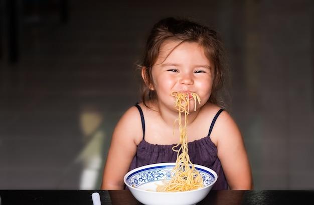 Menina linda criança comendo espaguete e sorrindo Foto Premium