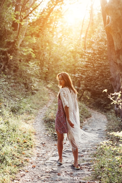 Menina linda e jovem caminha ao pé da montanha ao longo Foto gratuita