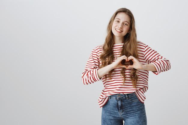 Menina linda e terna mostrando um gesto de coração, mostrando amor e carinho Foto gratuita