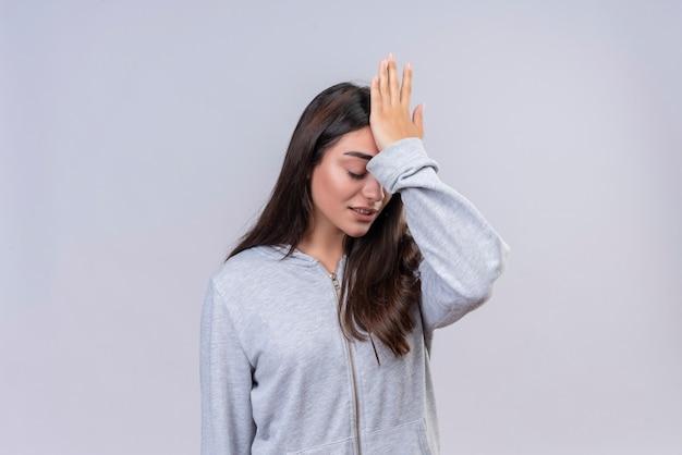 Menina linda em um capuz cinza tocando a cabeça por engano, parecendo um conceito de memória ruim confuso em pé sobre um fundo branco Foto gratuita
