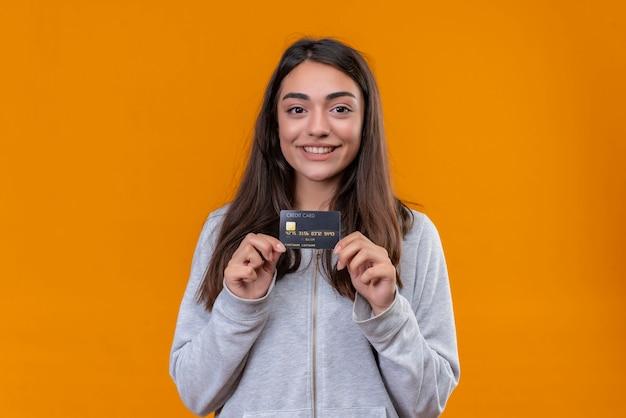 Menina linda em um casaco com carapuço cinza segurando um cartão de crédito e olhando para a câmera com um rosto simle em pé sobre um fundo laranja Foto gratuita