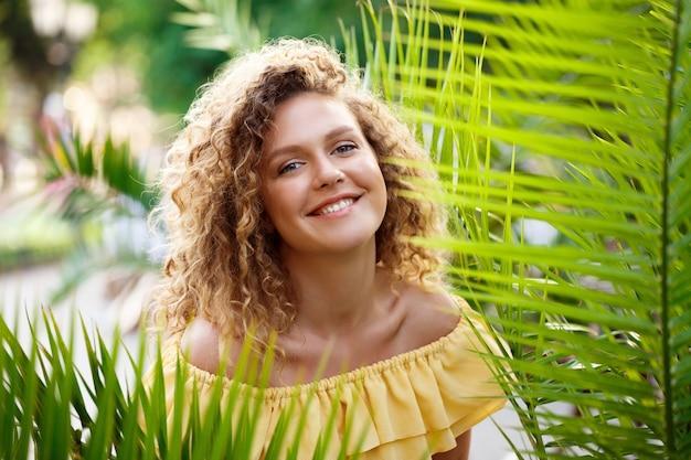 Menina linda num vestido amarelo posando no parque da cidade. Foto gratuita