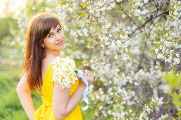 Menina linda sorrindo com um buquê de flores ao ar livre na primavera Foto Premium