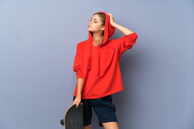 Menina loira adolescente skatista sobre parede cinza Foto Premium