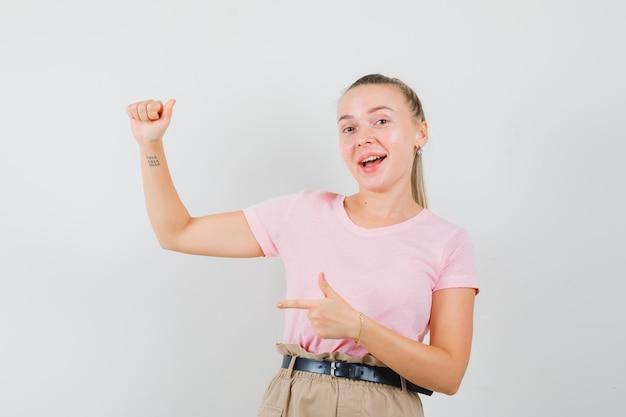 Menina loira apontando para algo que fingia estar segurando uma camiseta, calça e parecendo feliz, vista frontal. Foto gratuita