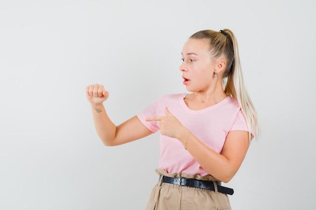 Menina loira apontando para algo que fingia estar segurando uma camiseta, calça e parecendo surpresa. vista frontal. Foto gratuita