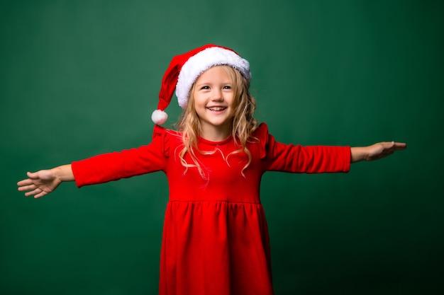 Menina loira com fantasia de papai noel sorrindo sobre fundo verde Foto Premium