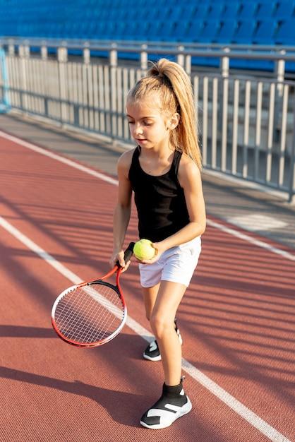 Menina loira com raquete de tênis e bola Foto gratuita