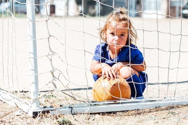 Menina loira com uniforme de futebol azul no gol com uma bola Foto Premium