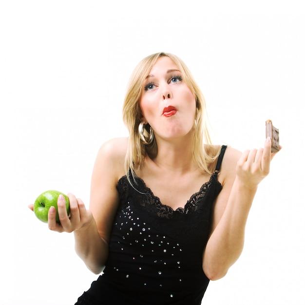 Menina loira comendo chocolate em vez de maçã Foto Premium
