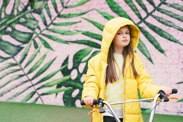 Menina loira de cabelo comprido em uma camisola amarela e jaqueta amarela Foto Premium