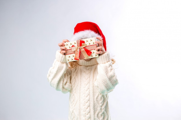 Menina loira de chapéu de papai noel segurando a caixa de presente Foto Premium