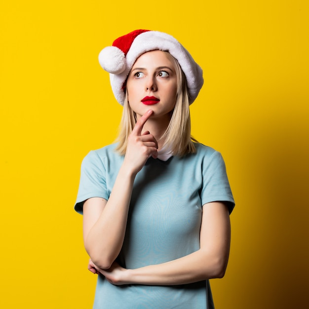 Menina loira de vestido azul e chapéu de papai noel no espaço amarelo Foto Premium