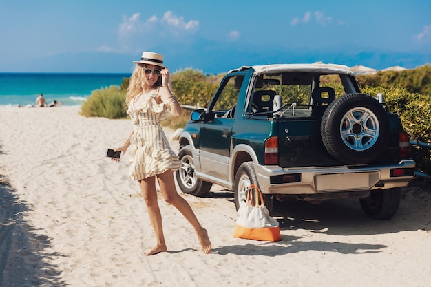 Menina loira de vestido listrado, posando na câmera na praia Foto Premium