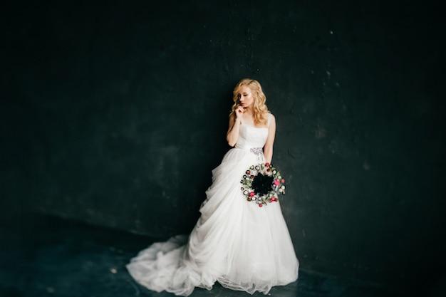 Menina loira europeia vestido de noiva branco segurando boquet de flores decorativas em fundo preto. Foto Premium