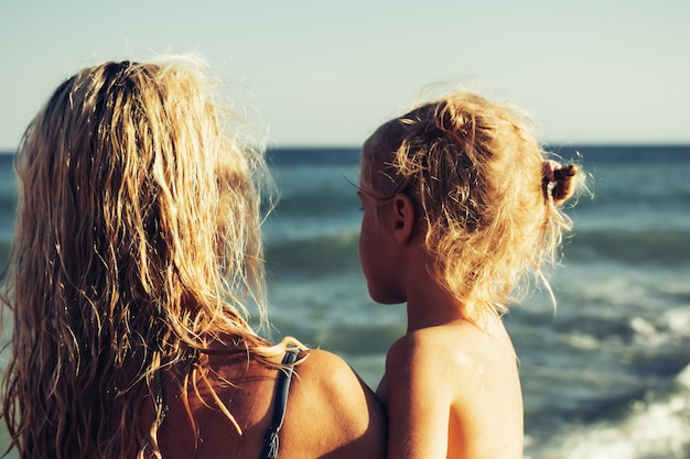 Menina loira feliz nos braços da mãe na praia. conceito de uma família feliz. férias concep Foto Premium