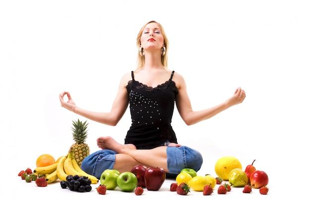 Menina loira meditando rodeado de frutas Foto Premium