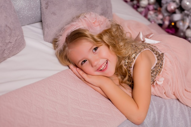 Menina loira na cama ao lado da árvore de natal. véspera de natal Foto Premium