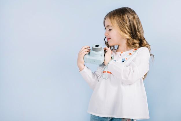 Menina loira olhando mini câmera instantânea segurando nas mãos contra o pano de fundo azul Foto gratuita
