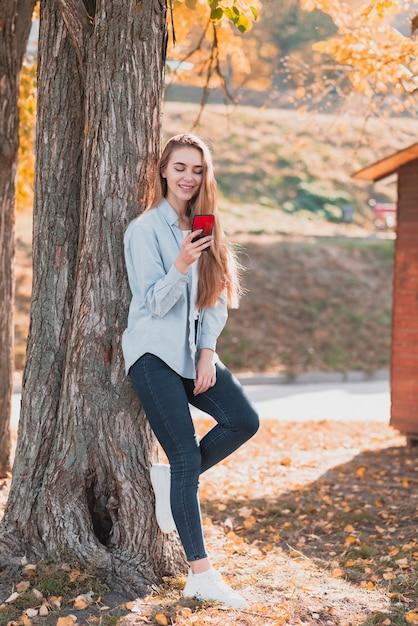 Menina loira olhando no telefone e sentado ao lado de uma árvore Foto gratuita