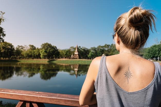 Menina loira olhando o lago na natureza no parque de sukhotai na tailândia. Foto Premium