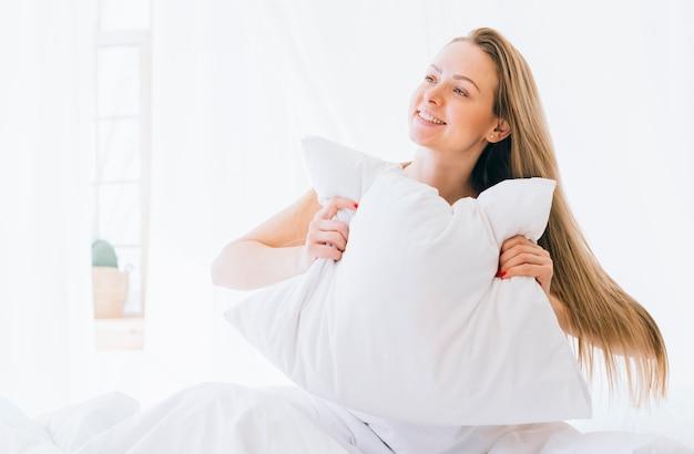 Menina loira posando na cama Foto gratuita
