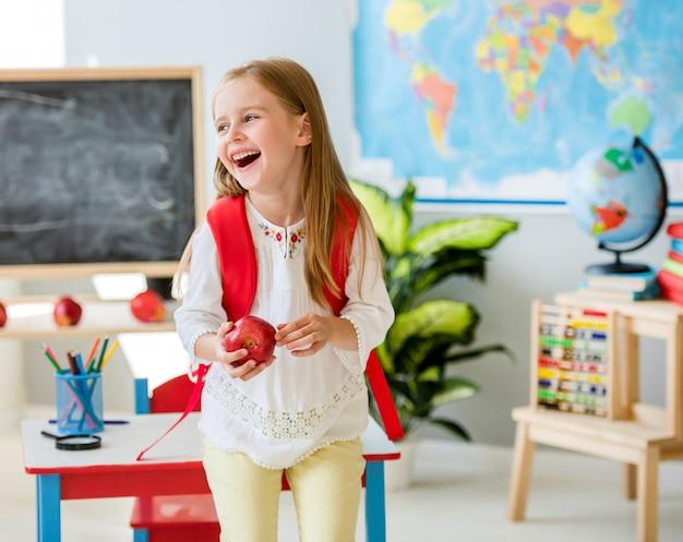 Menina loira rindo segurando uma maçã na sala de aula de escola Foto Premium