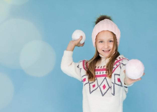 Menina loira se preparando para jogar uma bola de neve Foto gratuita