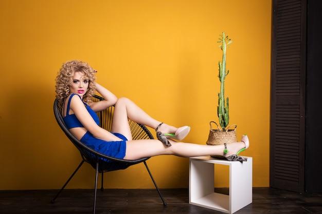 Menina loira, sentado em uma cadeira com um cacto Foto Premium