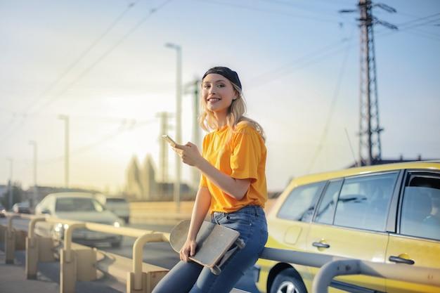 Menina loira sorridente com um skate na cidade Foto Premium