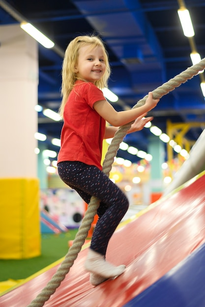 Menina loira subindo uma corda Foto gratuita