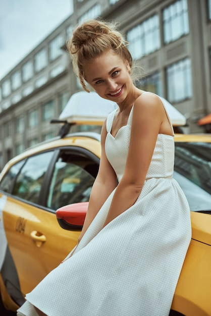 Menina loura com cabelo flyaway no fundo da rua de new york city com táxis de táxi. Foto Premium