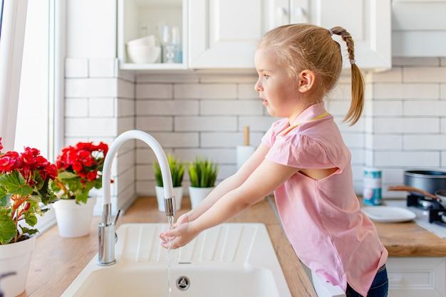 Menina loura da criança que lava as mãos na cozinha lingh antes de comer. conceito de higiene e saúde. Foto Premium
