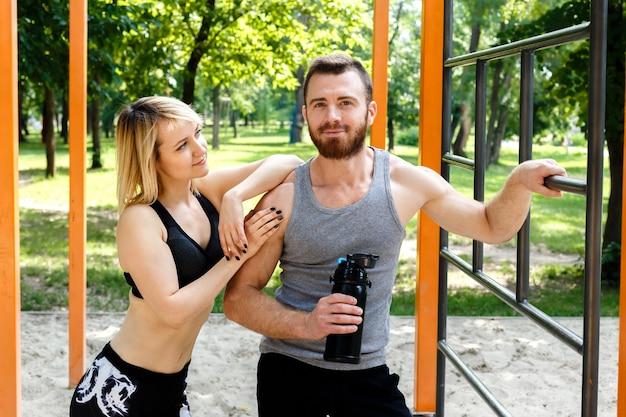 Menina loura desportiva e homem farpado que descansam após o treinamento do exercício em um parque exterior. homem segurando uma garrafa preta com água. Foto Premium