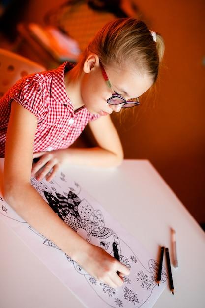 Menina loura no vestido cor-de-rosa e nos vidros pretos grandes que tiram papai noel. tema de ano novo Foto Premium